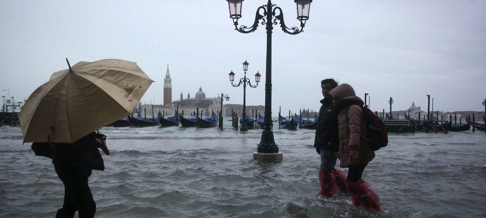 Foto: Varias personas caminan por las calles inundadas de Venecia tras unos días de fuertes lluvias en noviembre de 2012. (Reuters)