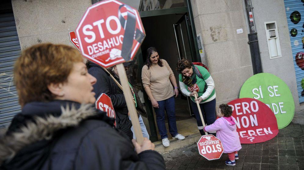 Foto: Una familia junto activistas del colectivo 'Stop Desahucios' después de que la plataforma consiguiese frenar el desahucio. (EFE)
