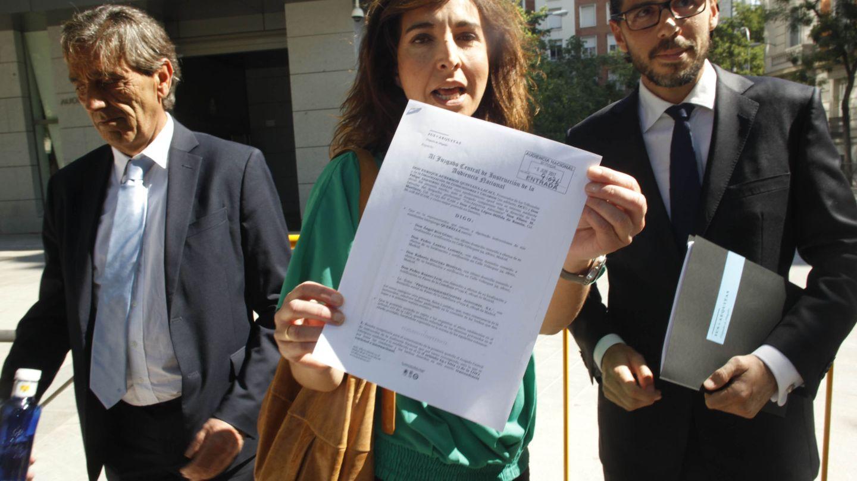 Ileana Izverniceanu, portavoz de OCU, muestra una querella en la entrada del juzgado. (EFE)