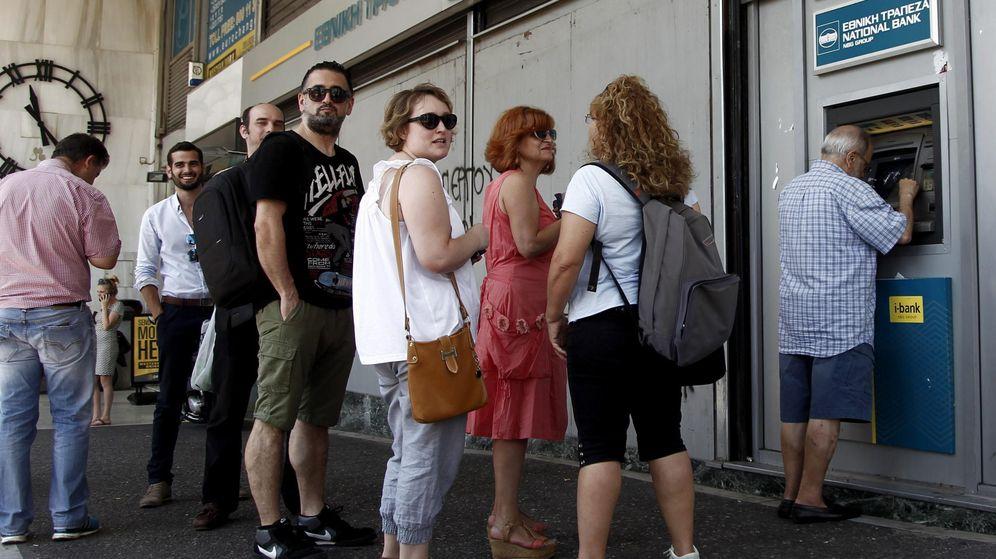 Foto: Atenienses hacen cola para retirar dinero de un cajero automático. (Efe)