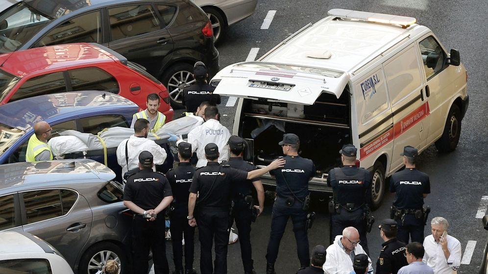 Foto: Funcionarios judiciales trasladan el cuerpo sin vida de una de las dos personas fallecidas esta mañana en la calle Sueca, donde un policía ha muerto acuchillado. (EFE)