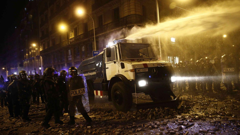 Un grupo de policías antidisturbios junto a la tanqueta de agua a presión. (EFE)