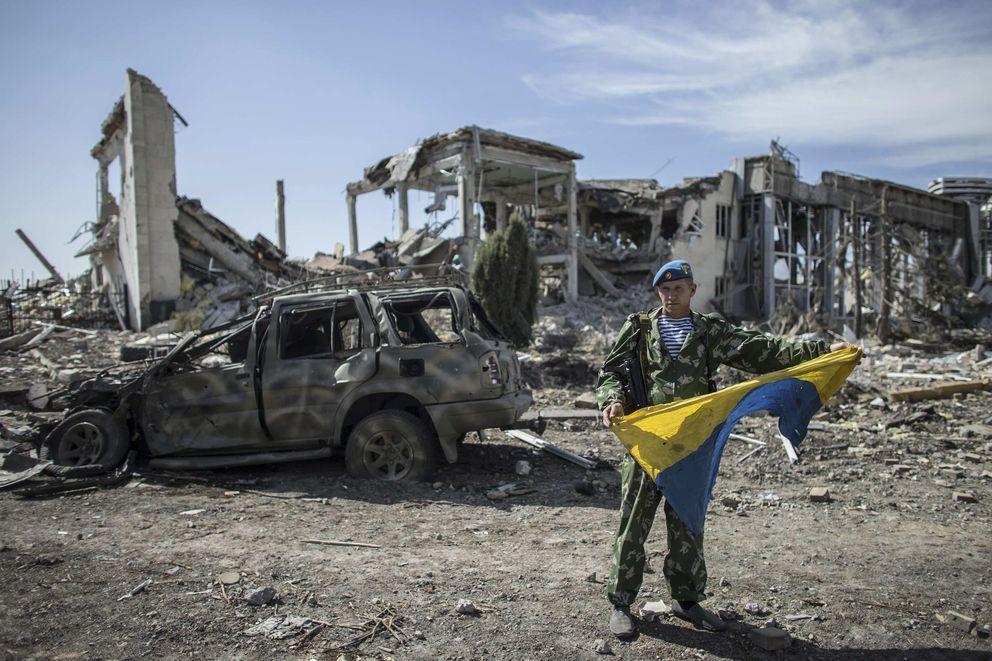 Foto: Yakut, un exparacaidista ruso, muestra una bandera ucraniana capturada en la toma del aeropuerto de Lugansk, en el Este de Ucrania. (Reuters)