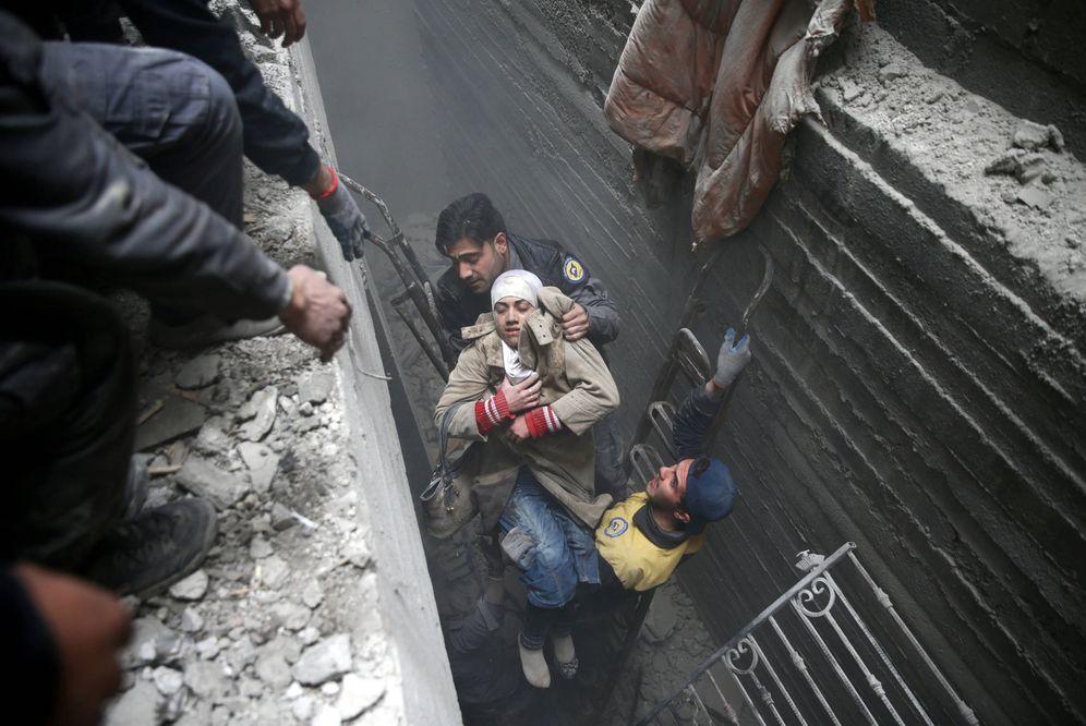 Foto: Miembros de la Defensa Civil rescatan a una mujer de un refugio en Duma, Guta Oriental, el 22 de febrero de 2018. (Reuters)