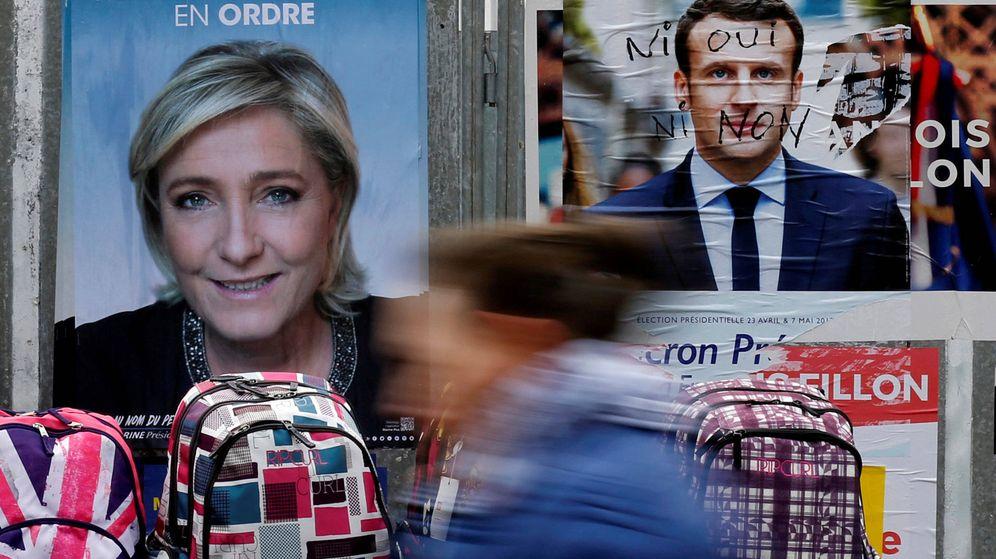 Foto: Una mujer pasa antes carteles de Le Pen y Macron en un mercado de Bethune, Francia. (Reuters)