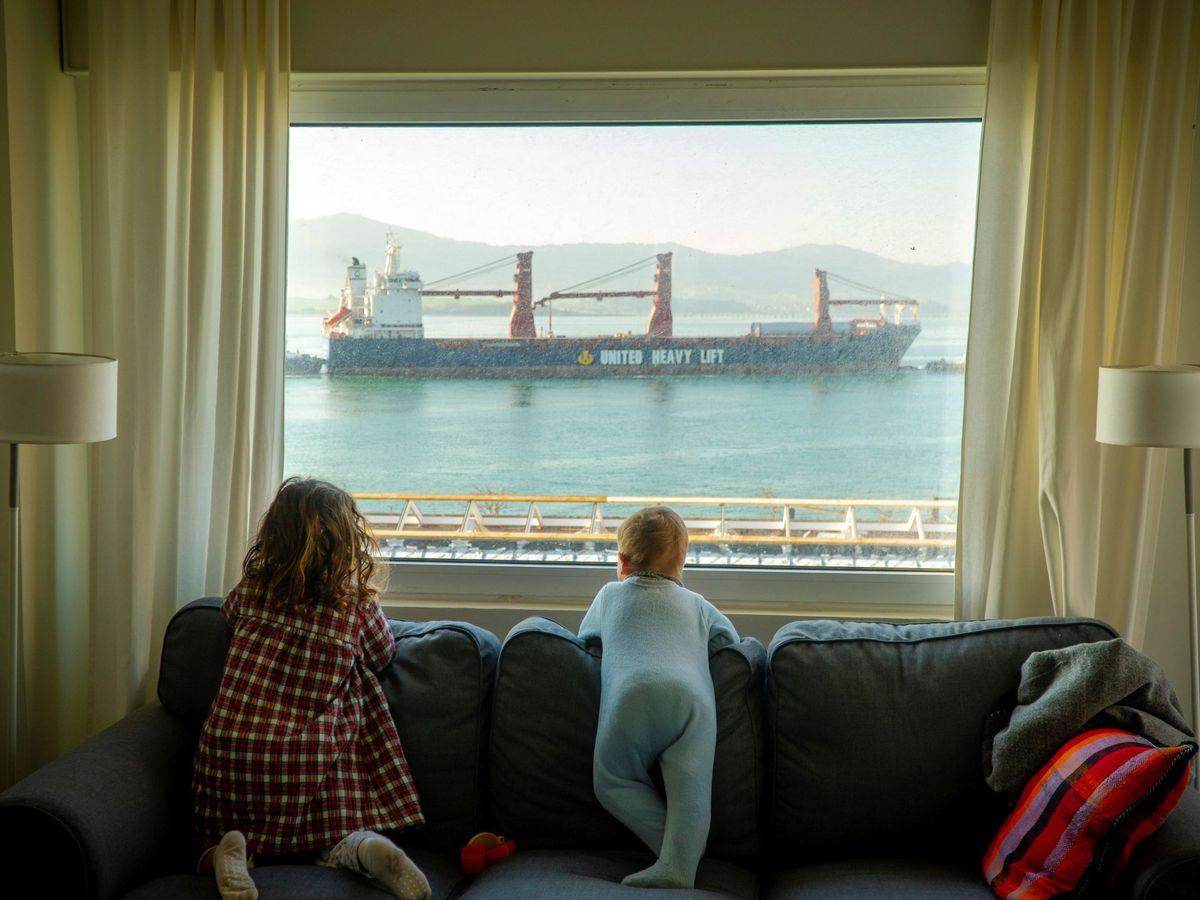 Foto: Dos niñas observan desde casa la entrada de barcos mercantes en la bahía de Santander, durante el 11º día de confinamiento, el pasado 25 de marzo. (EFE)