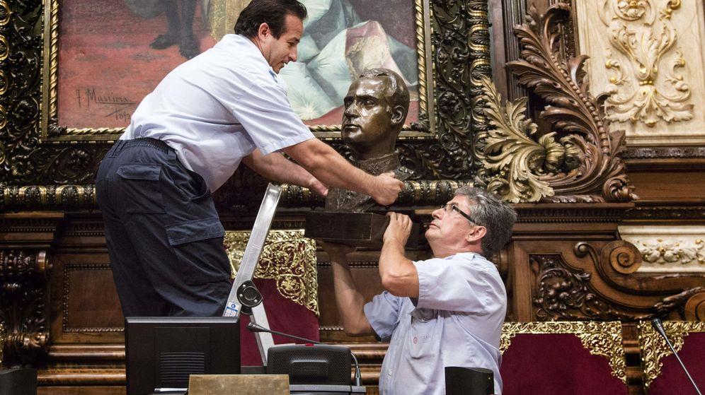 Foto: Dos operarios retiran el busto de Juan Carlos I del salón de plenos de Barcelona. (Efe)