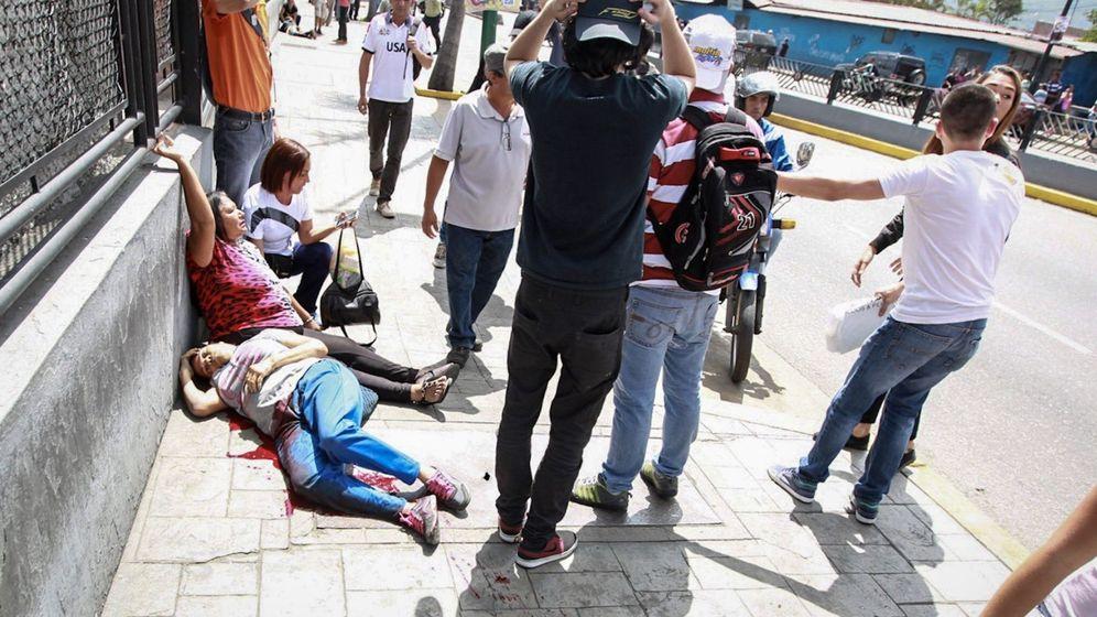 Foto: Dos mujeres yacen en el suelo durante un enfrentamiento entre un grupo de personas adeptas al oficialismo y personas opositoras al gobierno nacional. (EFE)