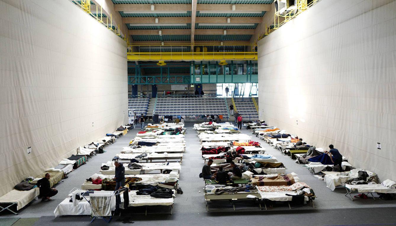 Foto: Migrantes descansan en un centro de refugio temporal instalado en un pabellón de deportes de Hanau, Alemania, en septiembre de 2015 (Reuters).