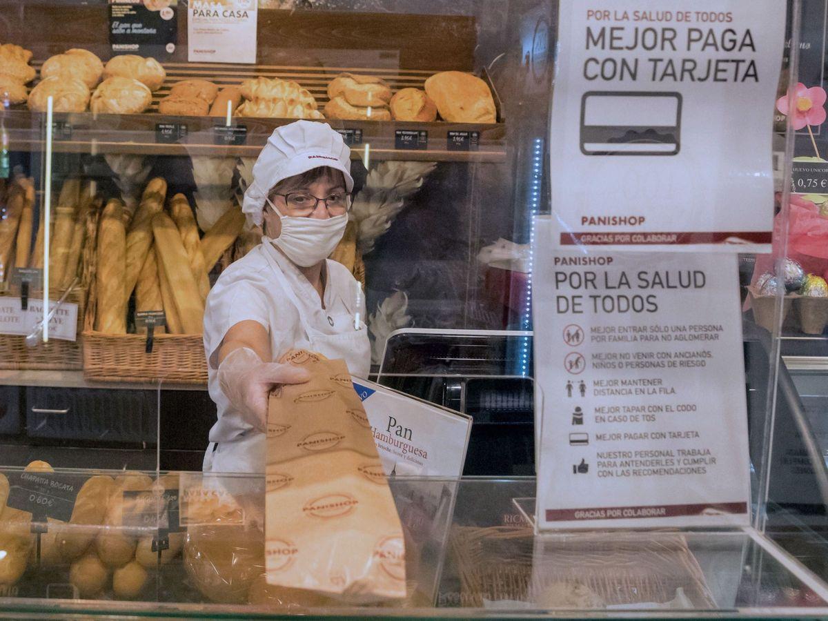 Foto: Un panadera sirve una barra tras una mampara de metacrilato. (Efe)