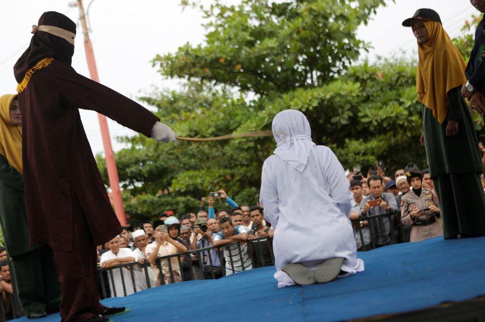 Foto: Una mujer recibe latigazos en público acusado de mantener relaciones sexuales fuera del matrimonio en Banda Aceh, Indonesia. (EFE)