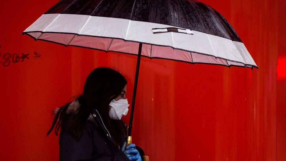 Foto: Una mujer camina bajo la lluvia con mascarilla y guantes en Málaga. (EFE)