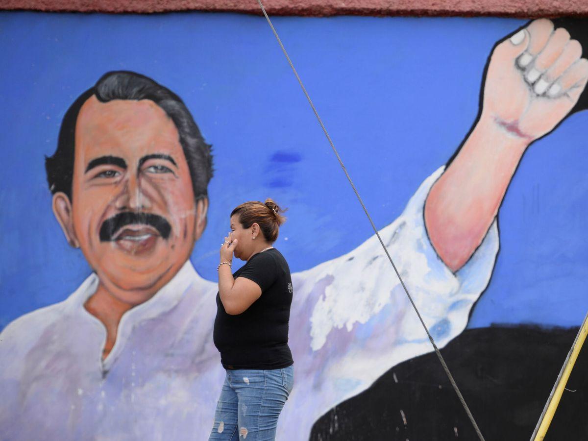 Foto: Una mujer camina frente a un mural de Daniel Ortega en Managua. (Reuters)