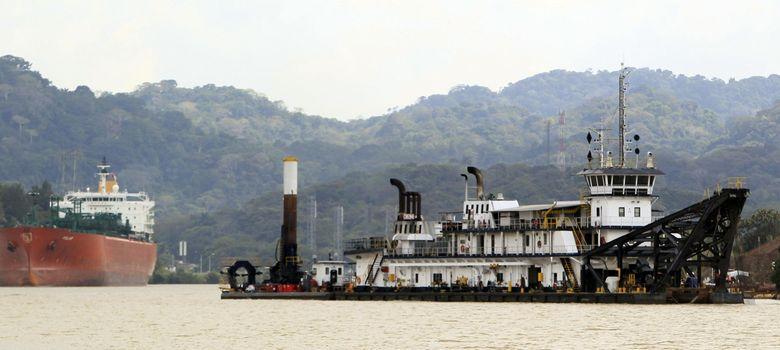 Foto: Una draga trabaja mientras buques transitan por el Corte Culebra en el canal de panamá. (EFE)