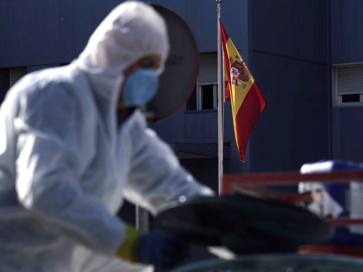 Foto: Un operario rellena un tanque con desinfectante, con una bandera a media asta de fondo. (EFE)