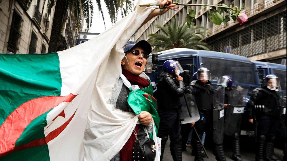 Foto: Policías montan guardia mientras una mujer agita una bandera argelina durante una protesta en Argel, el 8 de marzo de 2019. (Reuters)
