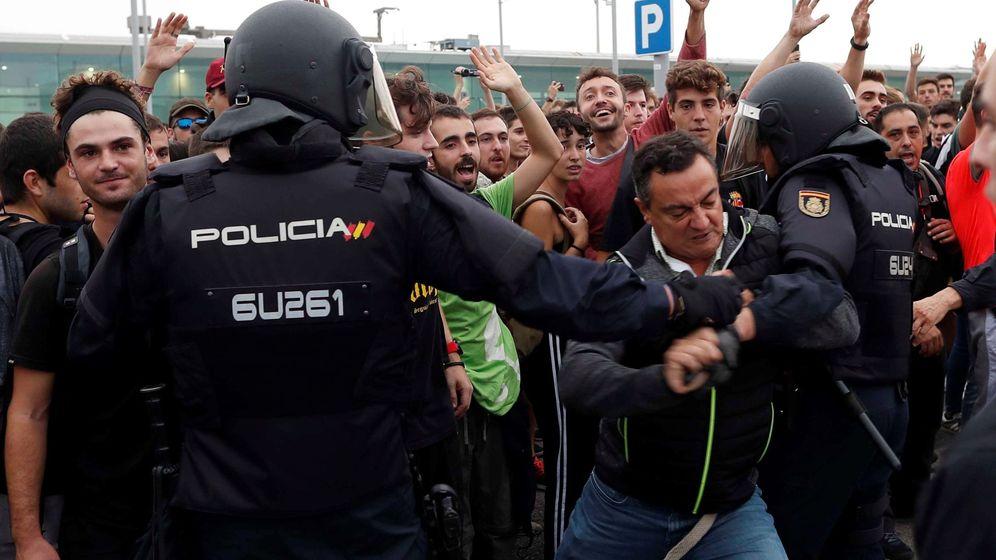 Foto: Un manifestante intenta romper el cordón policial en el Aeropuerto de El Prat. (EFE)