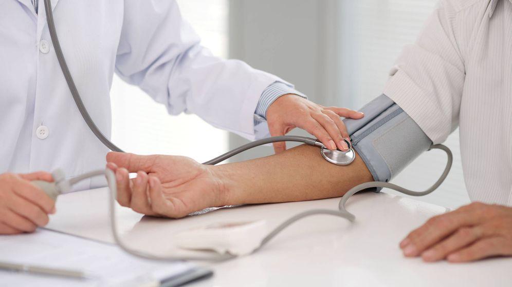 Foto: Un médico mide la tensión a un paciente para comprobar si tiene la presión arterial alta. (iStock)