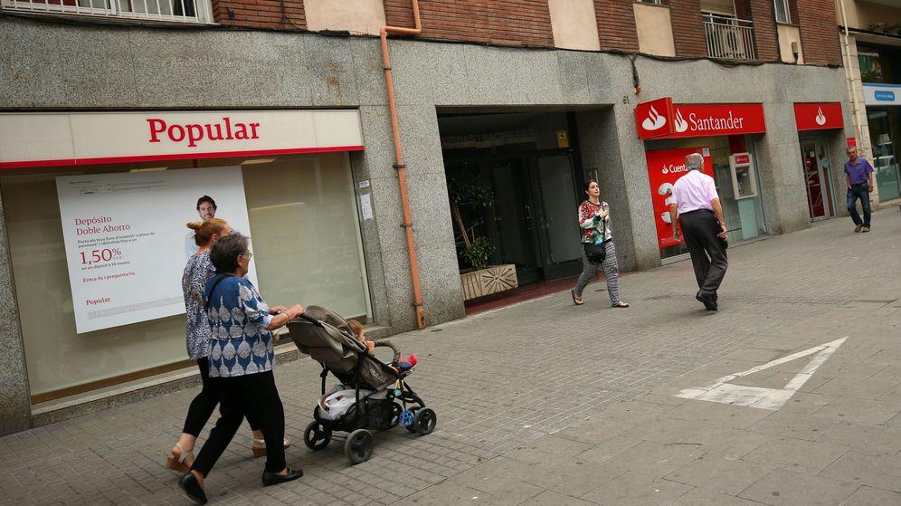 Foto: Varios peatones pasan por delante de unas oficinas del Banco Popular y del Banco Santander. (Reuters)