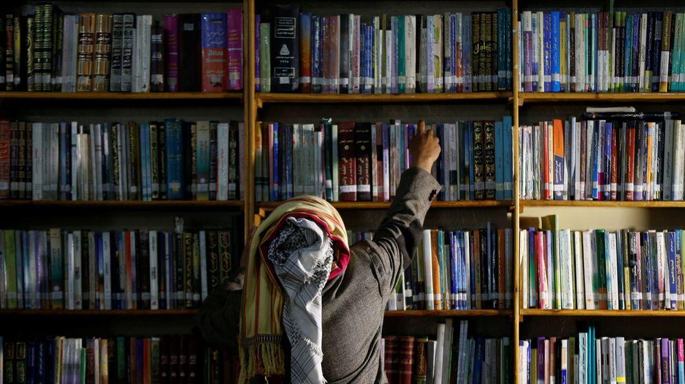 Foto: El autor yemení Mohammed al-Qaoud coge un libro de su biblioteca en Sanaa (Reuters)