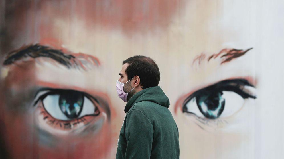 Foto: Un hombre porta una mascarilla frente a un mural. (Reuters)