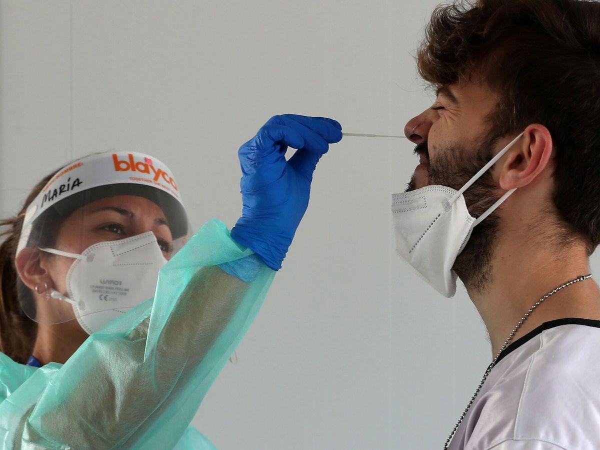Foto: Una enfermera realiza una PCR a un joven. (EFE)