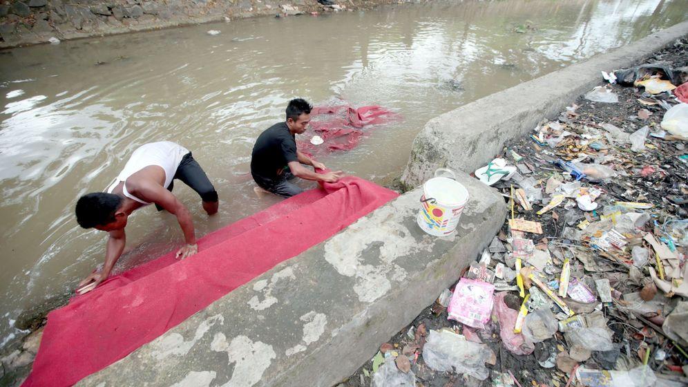 Foto: Unos hombres limpian una alfombra en un río contaminado de Indonesia. (EFE)