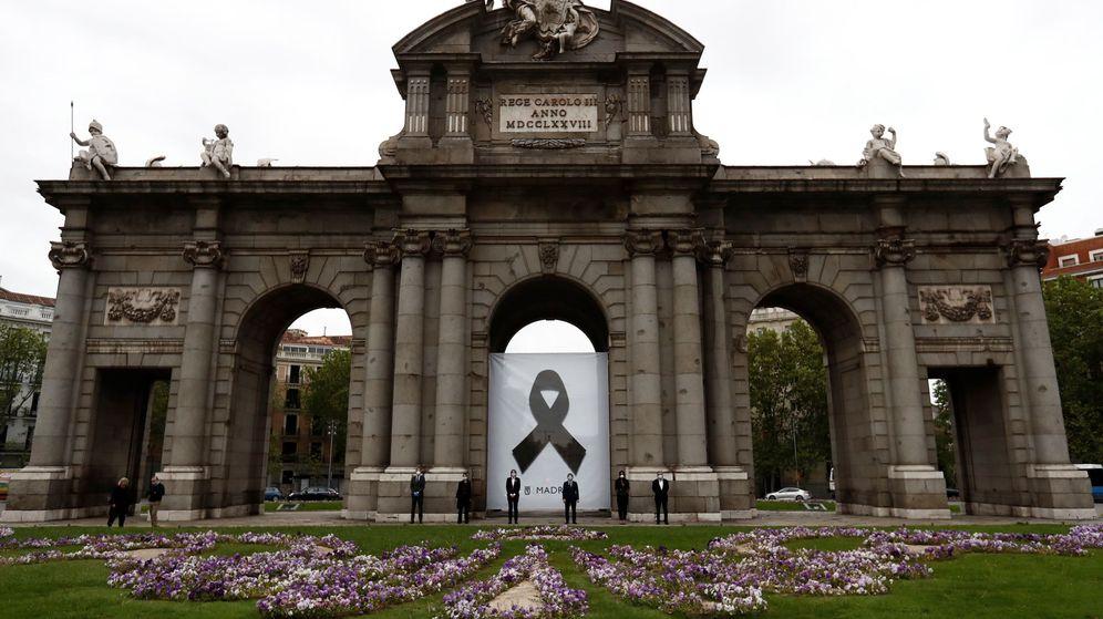Foto: Minuto de silencio por los fallecidos con coronavirus en la Puerta de Alcalá, en Madrid. (EFE)
