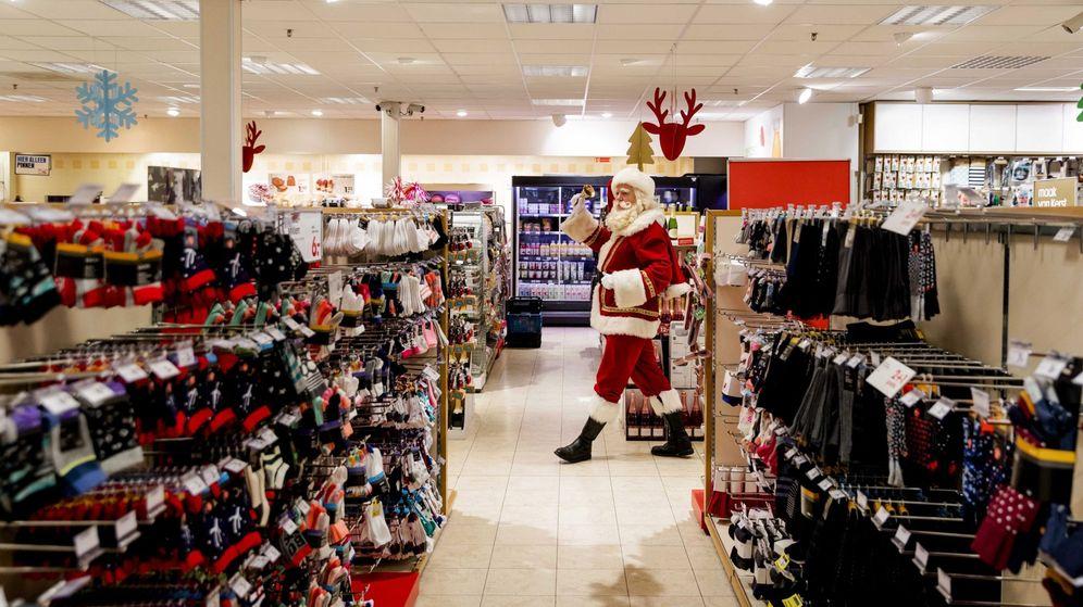 Foto:  Un hombre disfrazado de Papá Noel toca la campana en una tienda. (EFE)