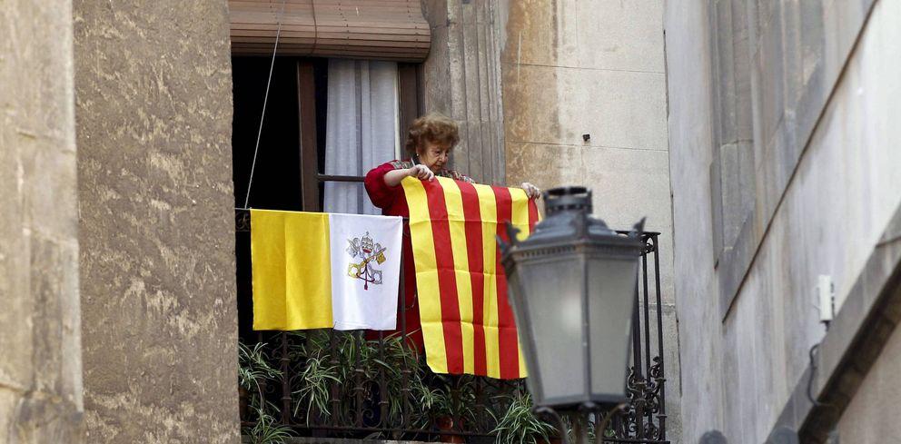 Foto: Una mujer coloca en su balcón una señera de Cataluña junto a otra del Vaticano, en 2010, durante la visita del anterior Papa, Benedicto XVI. (EFE)