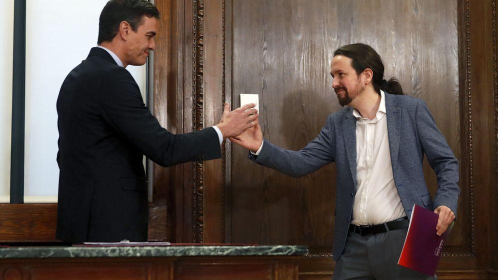 Foto: Pedro Sánchez (i) y Pablo Iglesias (d) estrechan sus manos durante el acto de firma del acuerdo programático del Gobierno de coalición. (EFE)