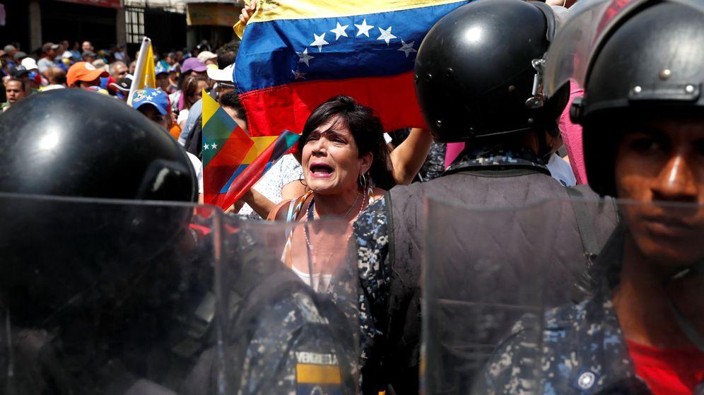 Foto: Una manifestante opositora se enfrenta a la policía en Caracas, este sábado. (Reuters)