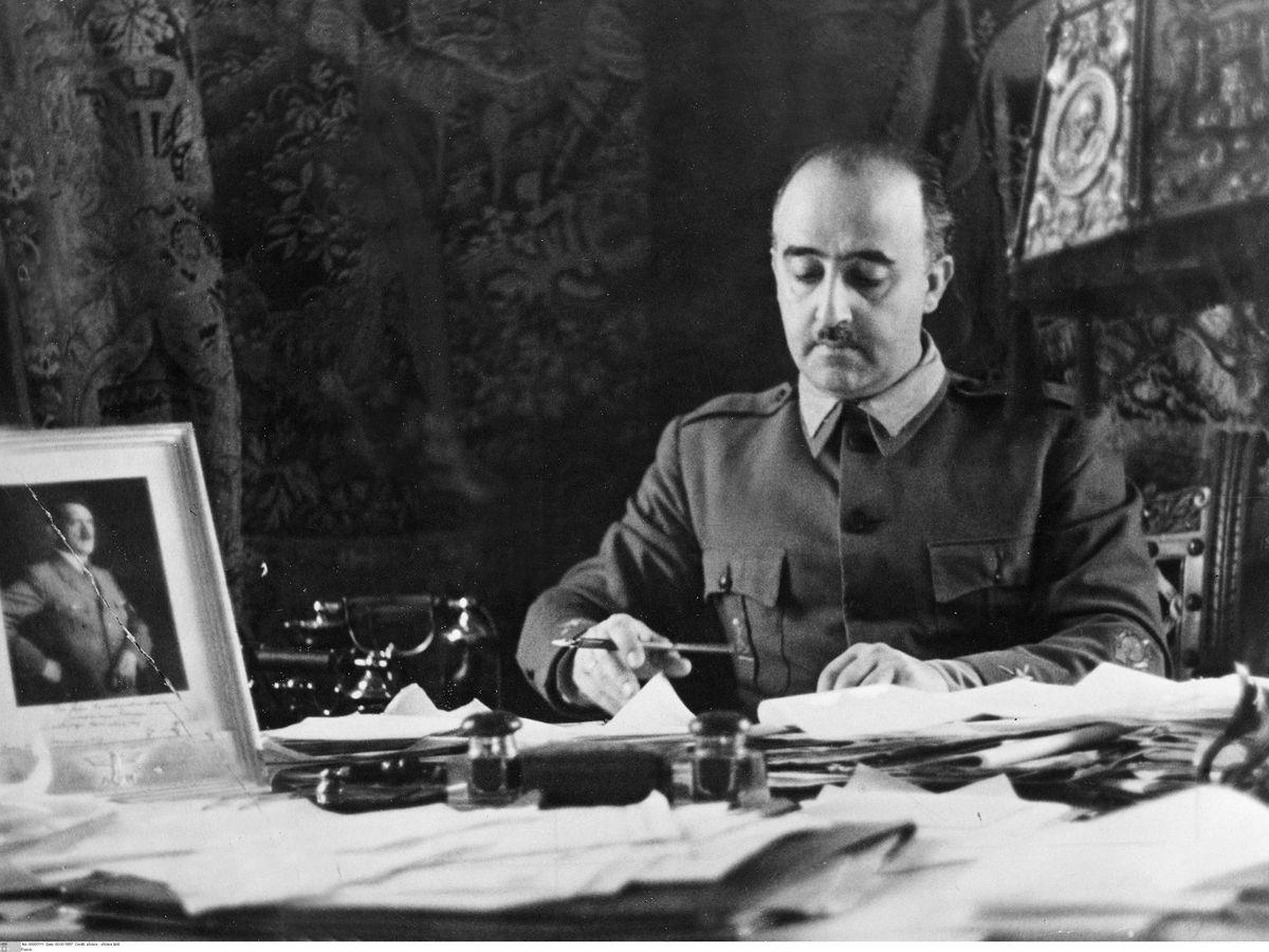 Foto: Franco, firmando documentos ante la atenta mirada de un retrato de Hitler. (Cordon Press)