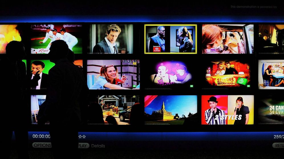 Foto: Dos personas observan varias pantallas de televisión. (EFE)