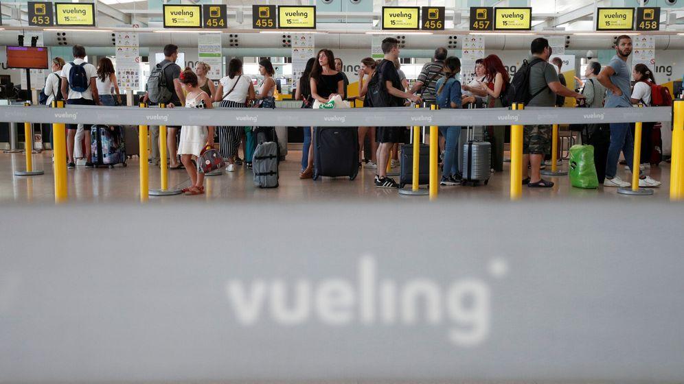Foto: Foto de archivo de personas que hacen cola frente al mostrador de Vueling. (Reuters)