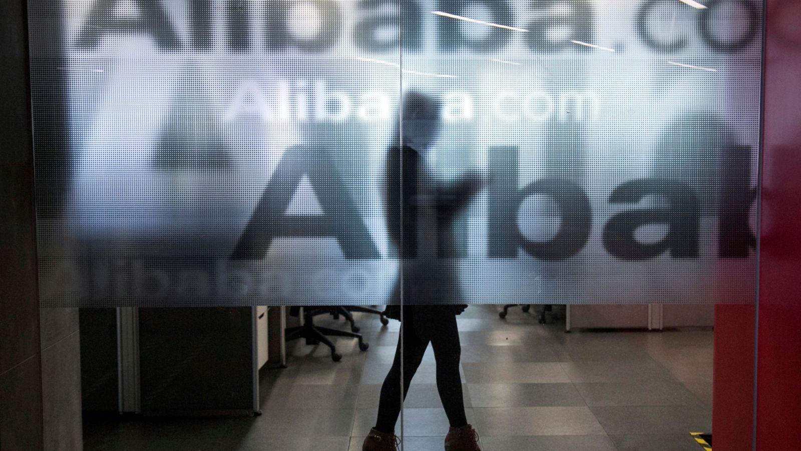 Foto: Una trabajadora, detrás de un logotipo de Alibaba en las oficinas de la compañía en Hangzhou. (Reuters)