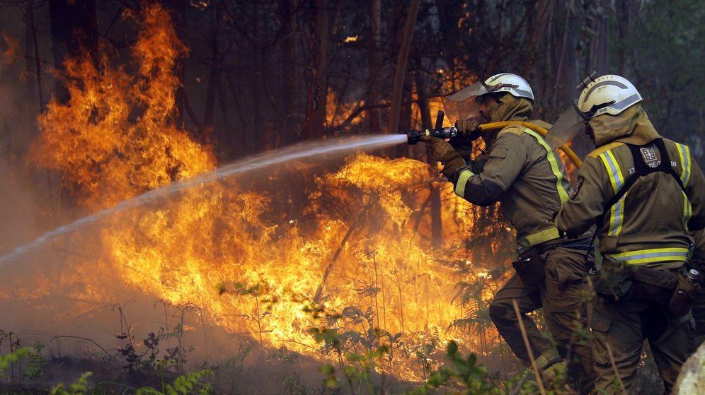 Foto: Los bomberos apagan uno de los numerosos focos del incendio en la localidad coruñesa de Rianxo. (EFE)