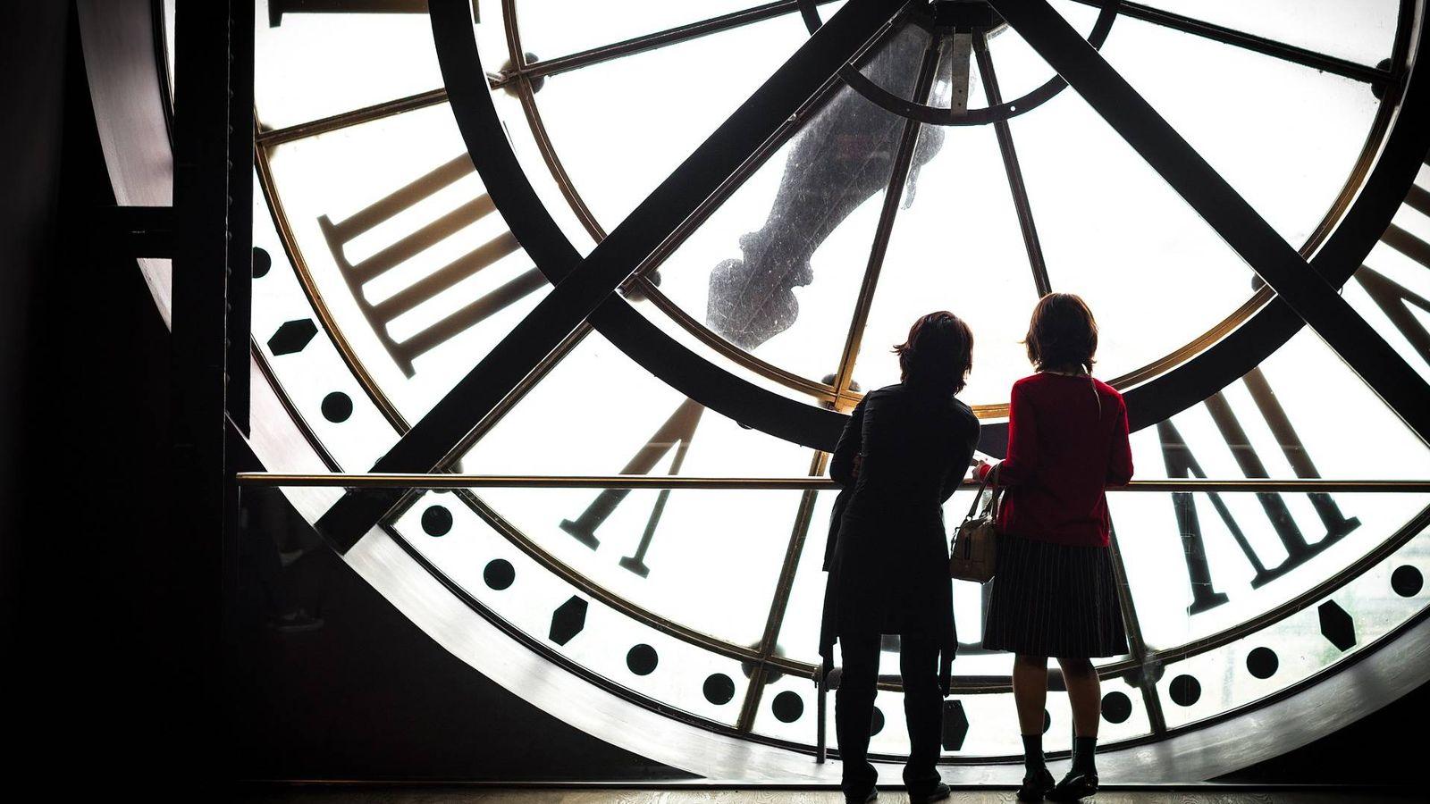 Foto: Dos turistas contemplan un gran reloj por dentro. (Pixabay)