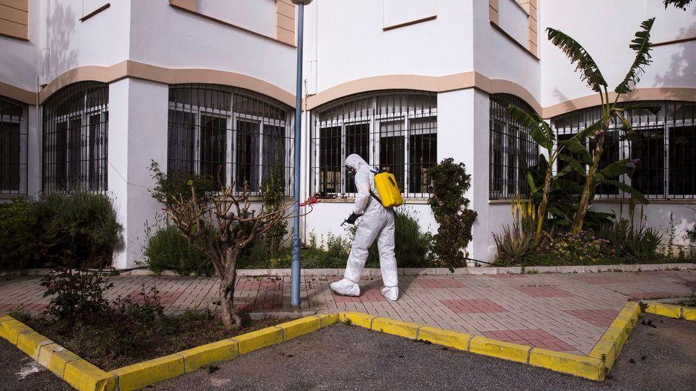 Foto: Un efectivo de la UME durante la operación de desinfección en la zona de estacionamiento de una residencia de ancianos. (EFE)