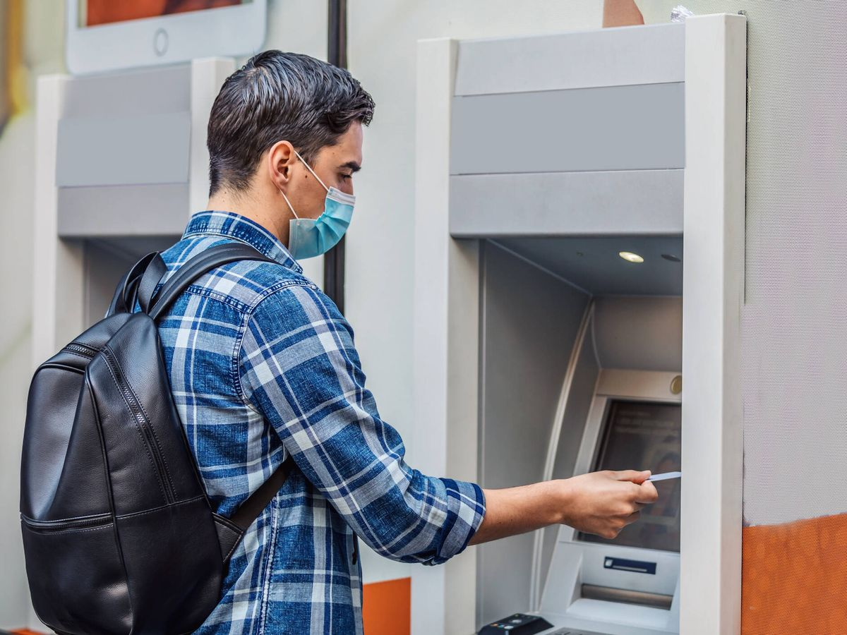 Foto: Un hombre saca dinero de un cajero. (iStock)