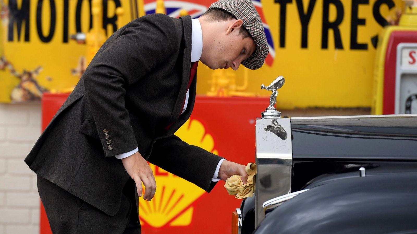 Foto: Un hombre limpia la carrocería de un Rolls Royce en el certamen de coches históricos de Goodwood, Inglaterra. (Reuters)