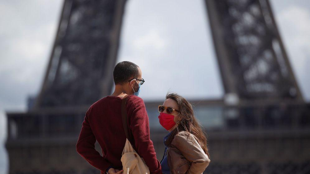Foto: Una pareja con máscaras protectoras pasea cerca de la Torre Eiffel. (EFE)