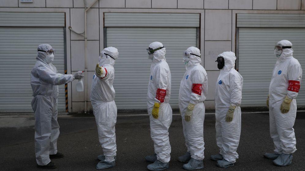 Foto: Voluntarios son desinfectados en Wuhan. (Reuters)