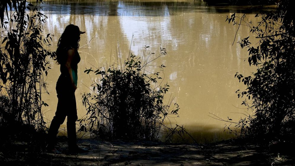 Foto: Una joven observa el caude del Guadiamar a su paso por la localidad de Aznalcóllar. (EFE)