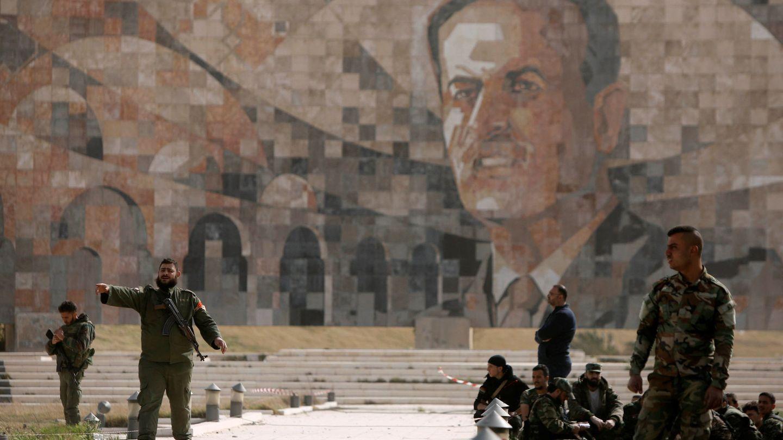 Soldados del ejército sirio frente a un mural de Hazef al Asad, padre del actual presidente, en Harasta, a finales de marzo. (Reuters)