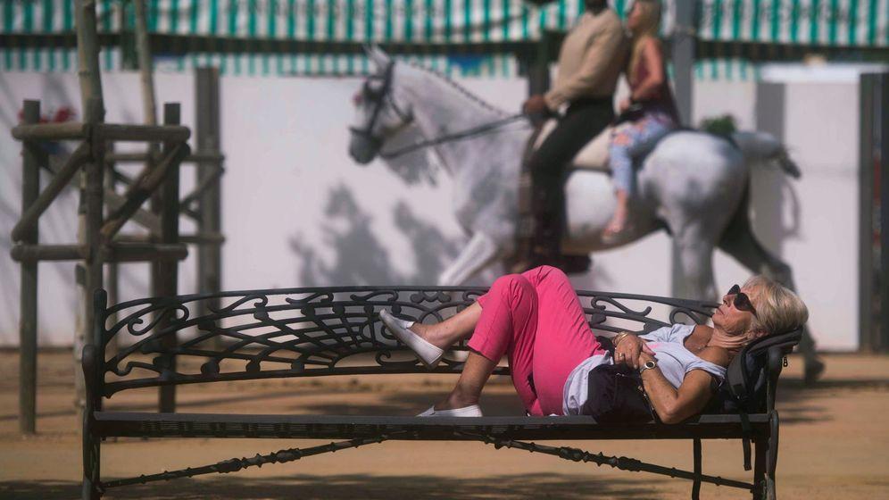 Foto: Una mujer echa un sueñecito en un banco de la feria de Córdoba. (EFE)