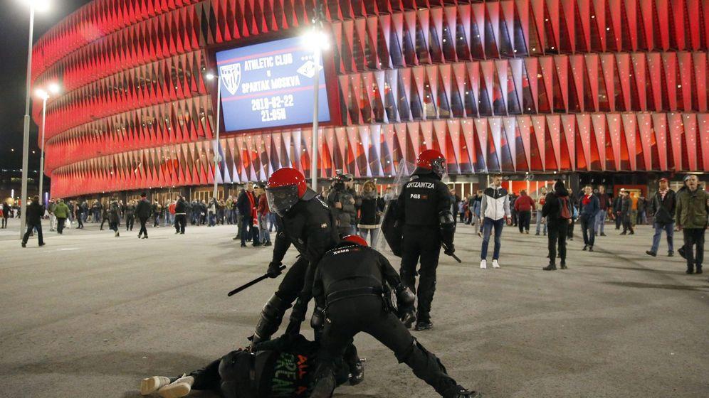 Foto: Agentes de la brigada móvil de la Ertzaintza, detienen a un aficionado tras varias cargas momentos antes del partido. (EFE)