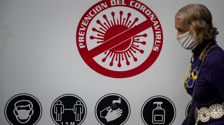 Una mujer camina frente a un aviso que promueve medidas de protección en Caracas. (EFE)
