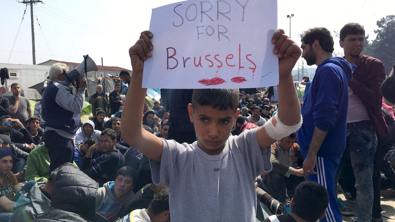 Foto: Un niño refugiado muestra un cartel expresando sus condolencias por el atentado de Bruselas (Reuters)