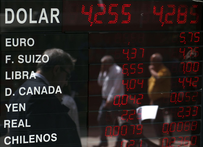 Foto: Argentinos reflejados en un panel con los tipos de cambios de diversas divisas extranjeras en Buenos Aires (Reuters).